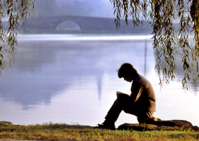 A man reading by a lake.